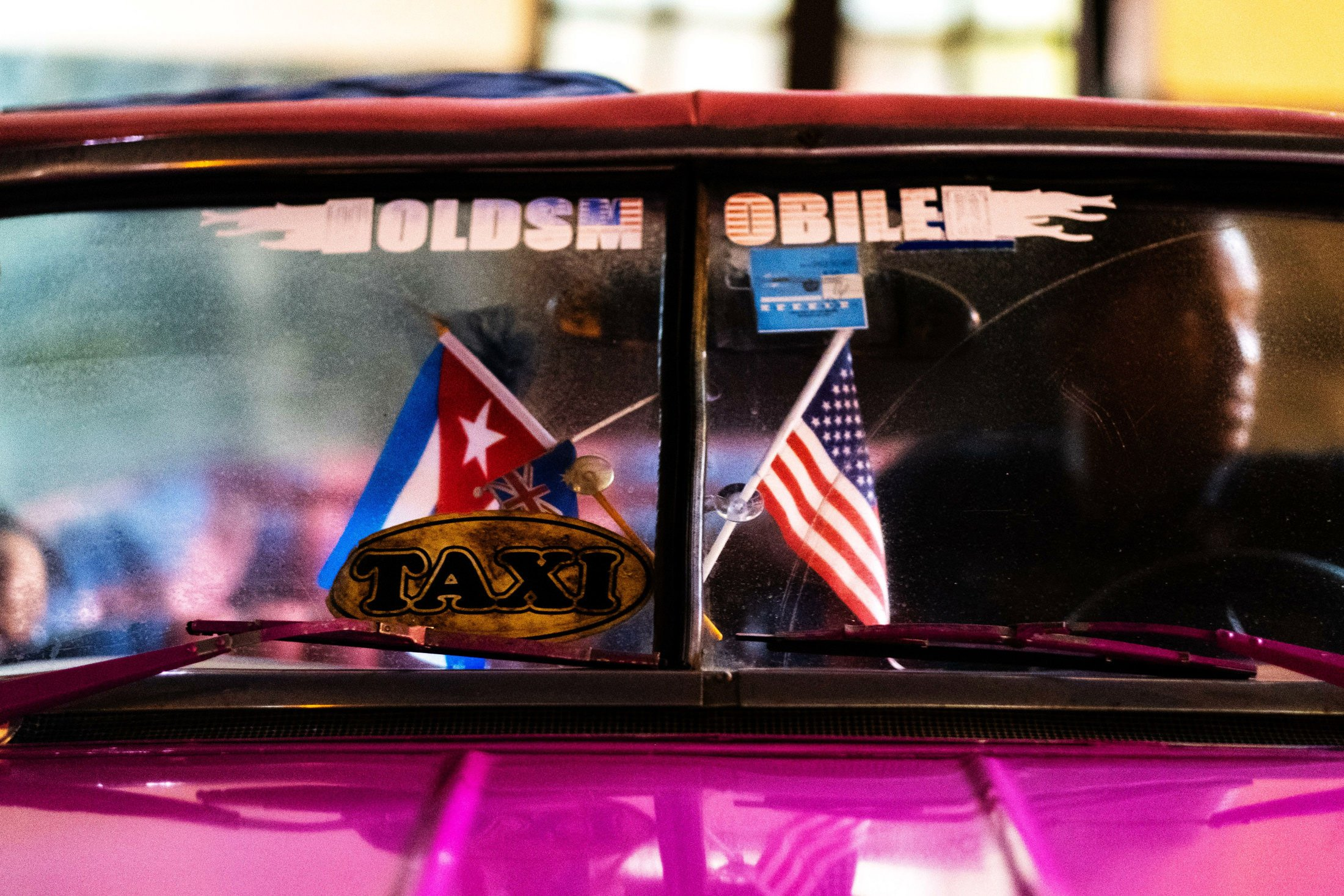 Pink Cuban car with two flags