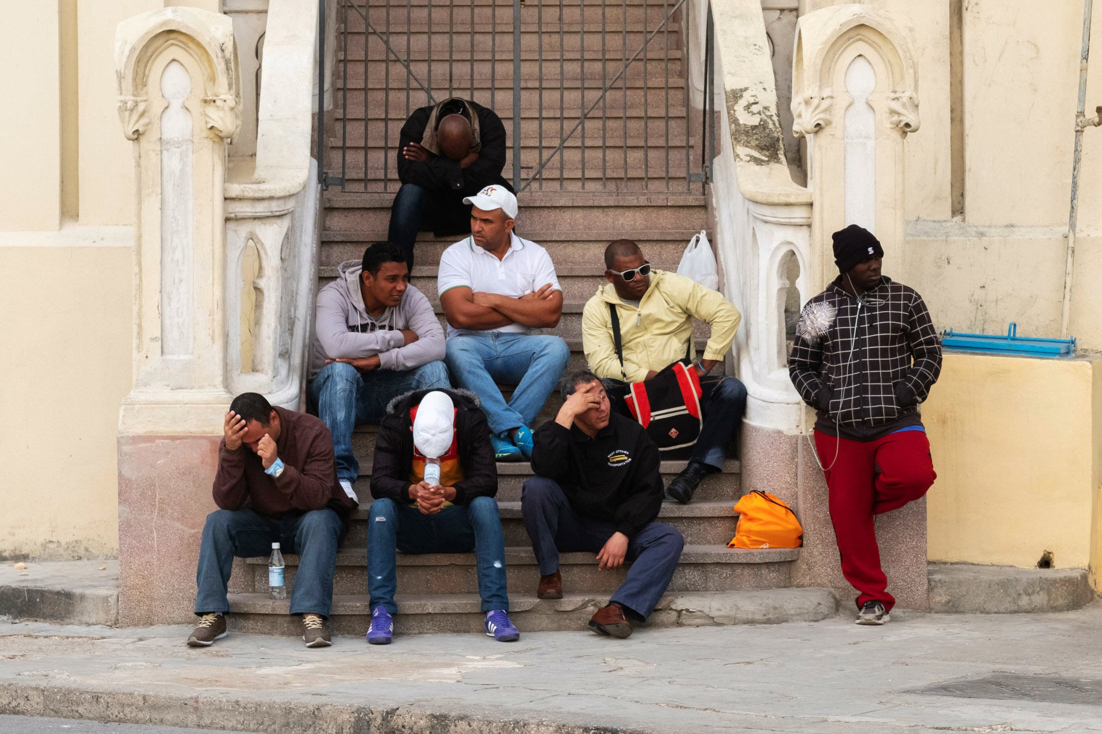 a group of men sat on the steps in the centre of Cuba