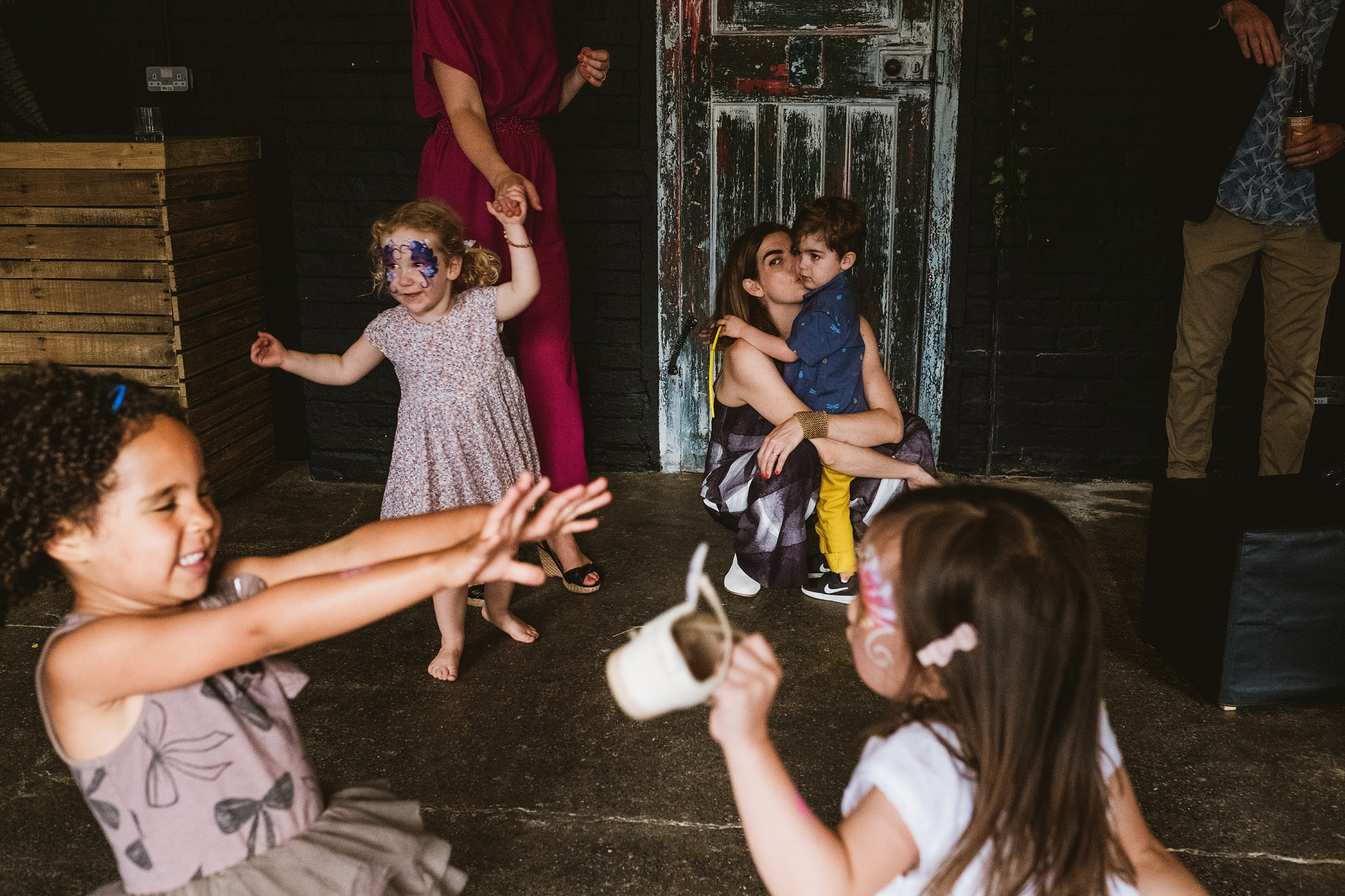 family party photography in London. Left of the frame a young girl holds her arms out with her eyes closed. Opposite her another girl in a white dress and facepaint is interacting with her holding a small white basket. Behind a mother is kissing her child, a man is opening a beer and a woman in a pink dress whose face we cannot see is holding the hands of another little girl wearing facepaint and a pretty dress. At the back of a frame is a chalk painted door.