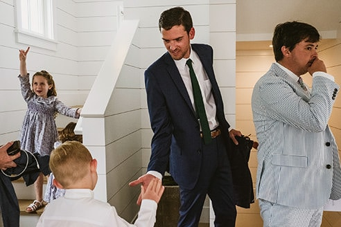 Groom, facing towards camera high fives a young boy with his back to the camera whilst to the left a little girl holds her arm in the air whilst leaning against a bannister. To the right a man in a light grey suit holds his hand to his mouth. This is an example of a photojournalist style wedding photograph