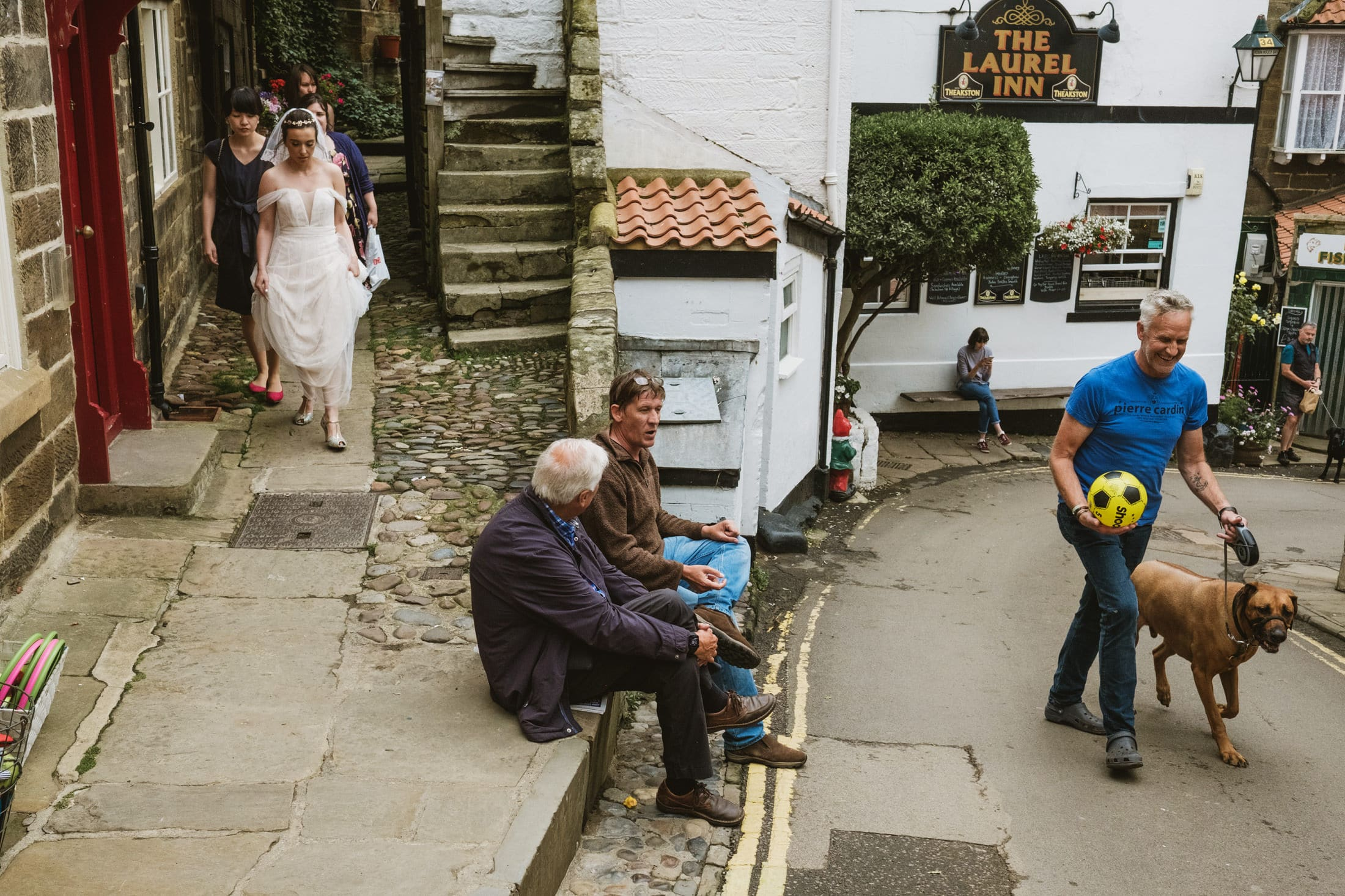 Bride on the way to ceremony going through Robin's Hood Bay.