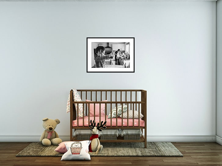 Framed family photo mounted on the wall above a baby's cot and toys