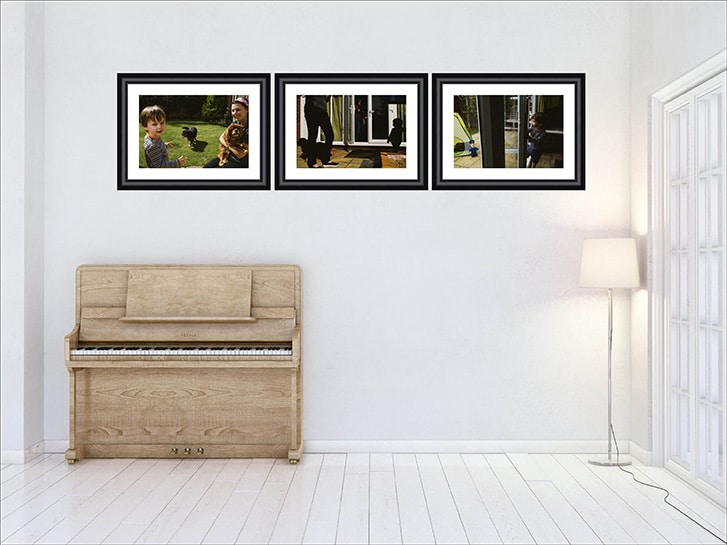 Family Photography showcase. 3 Mounted family photographs in a row in black frames and white mounts on the wall of a room decorated in white with a piano and lamp