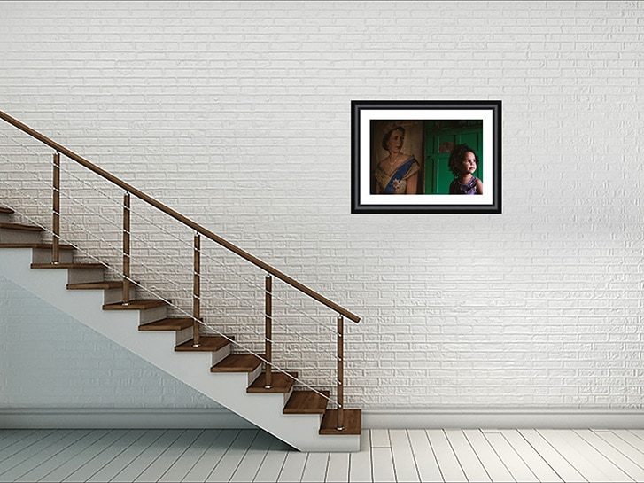 Wall mounted family photography. Photo of a young girl and portrait of the queen on a white brick wall with staircase to the left of the frame
