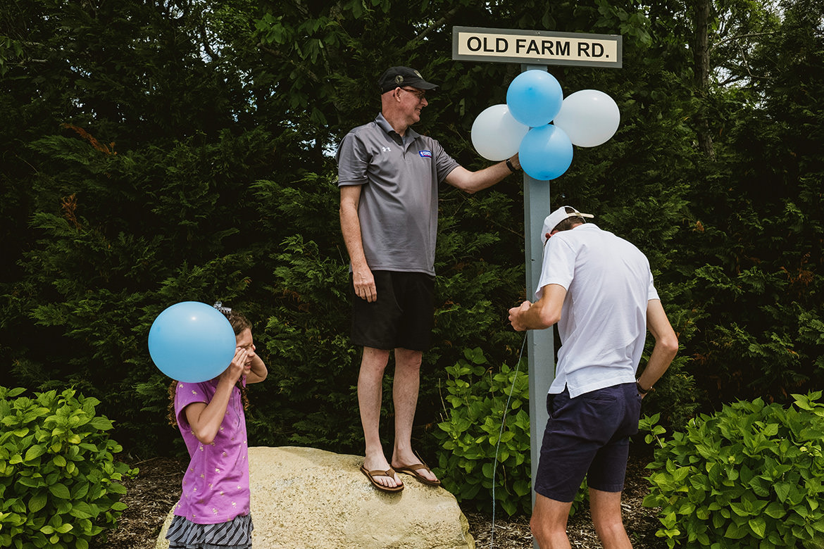 Family photography captured in Nantucket USA. A man stands on a boulder attaching blue and white balloons to a signpost that reads Old Farm Road. Below the sign a man in shorts, T-shirt and a baseball cap looks for something in his pocket. On the left of the frame a girl holds a blue balloon.