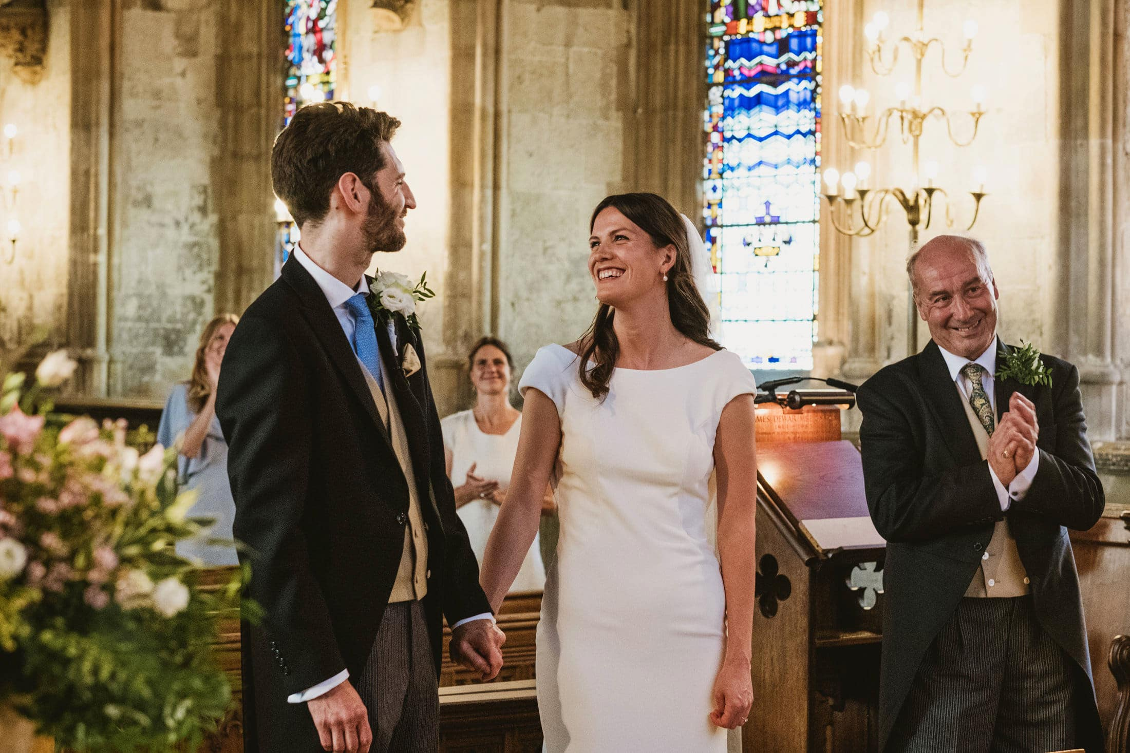 Groom (left) & bride (centre) smile and hold hands as they are pronounced husband and wife at a London church micro wedding. (Right) the father of the bride smiles and claps along with other guests framed in the background