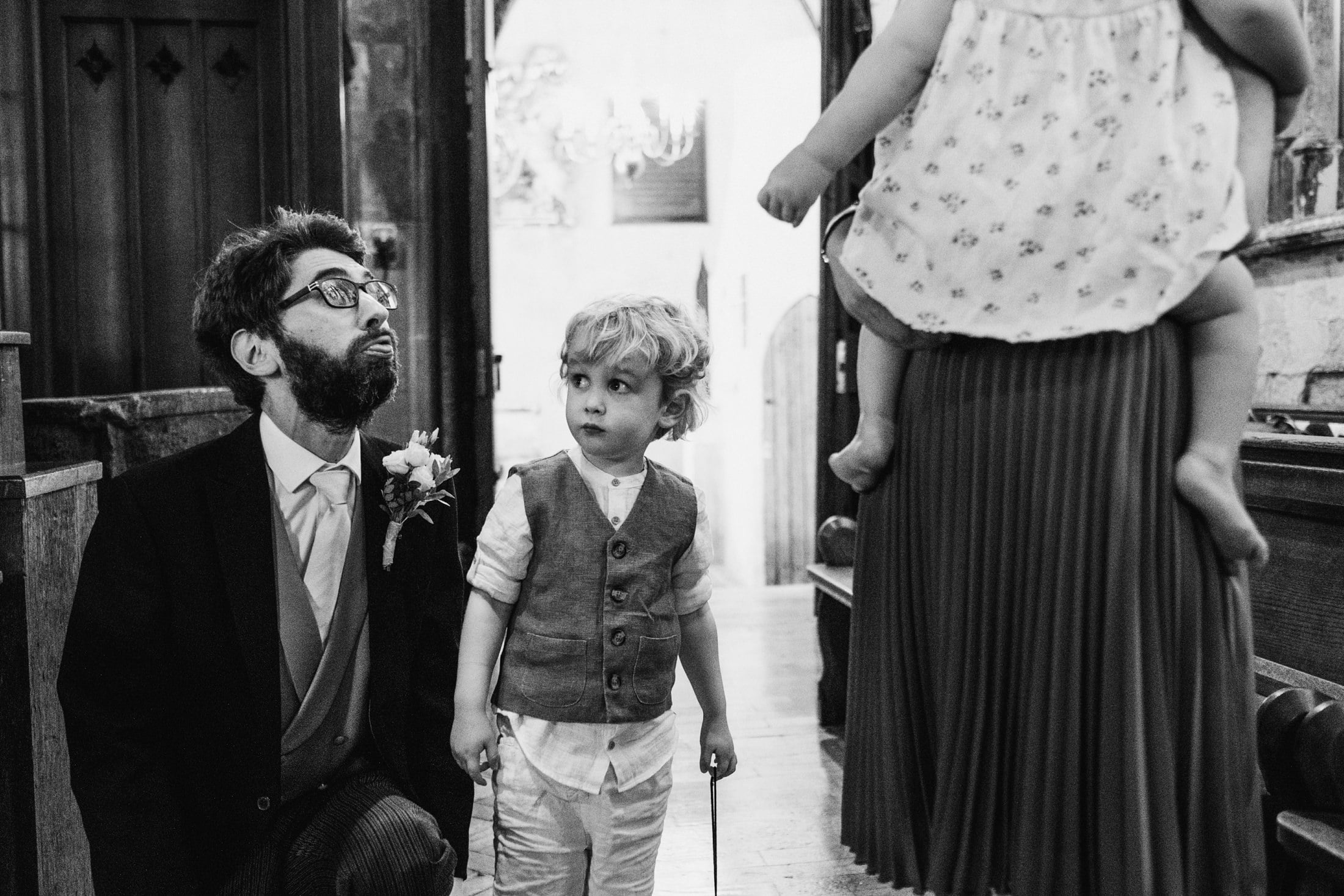 Groomsman crouches beside a little boy in a London church wedding. On the right we see the legs of a little girl being held in a woman's arms