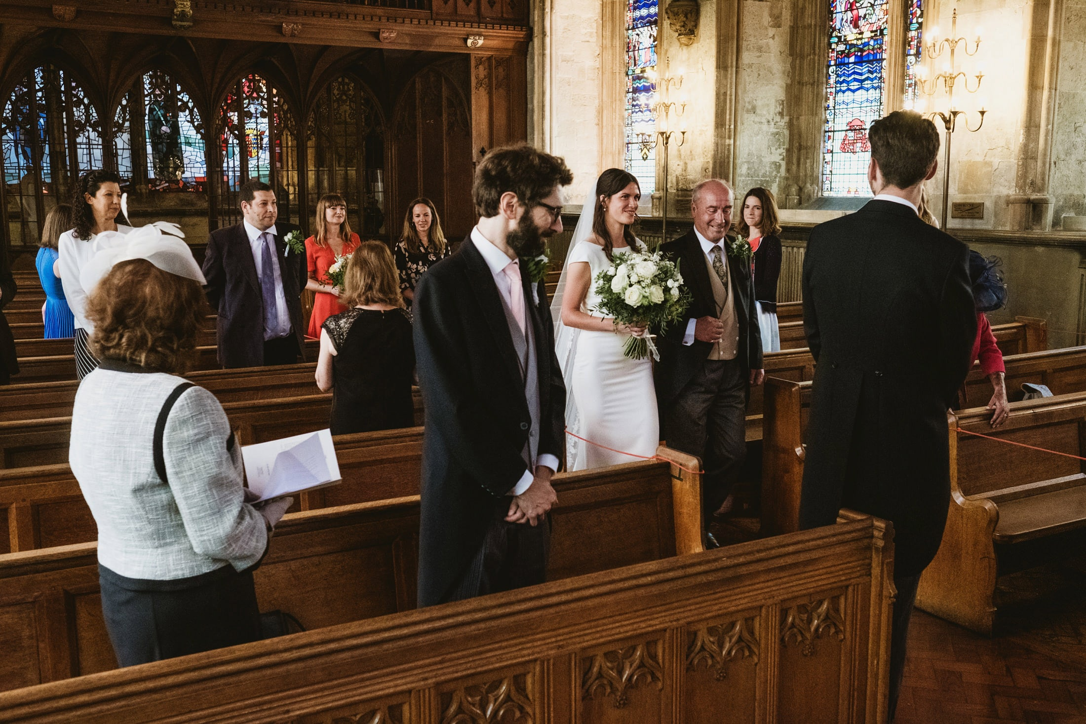 Guests (socially distanced) stand as the bride and her father make their entrance and approach the waiting groom. Wedding photograph from a micro wedding in London.