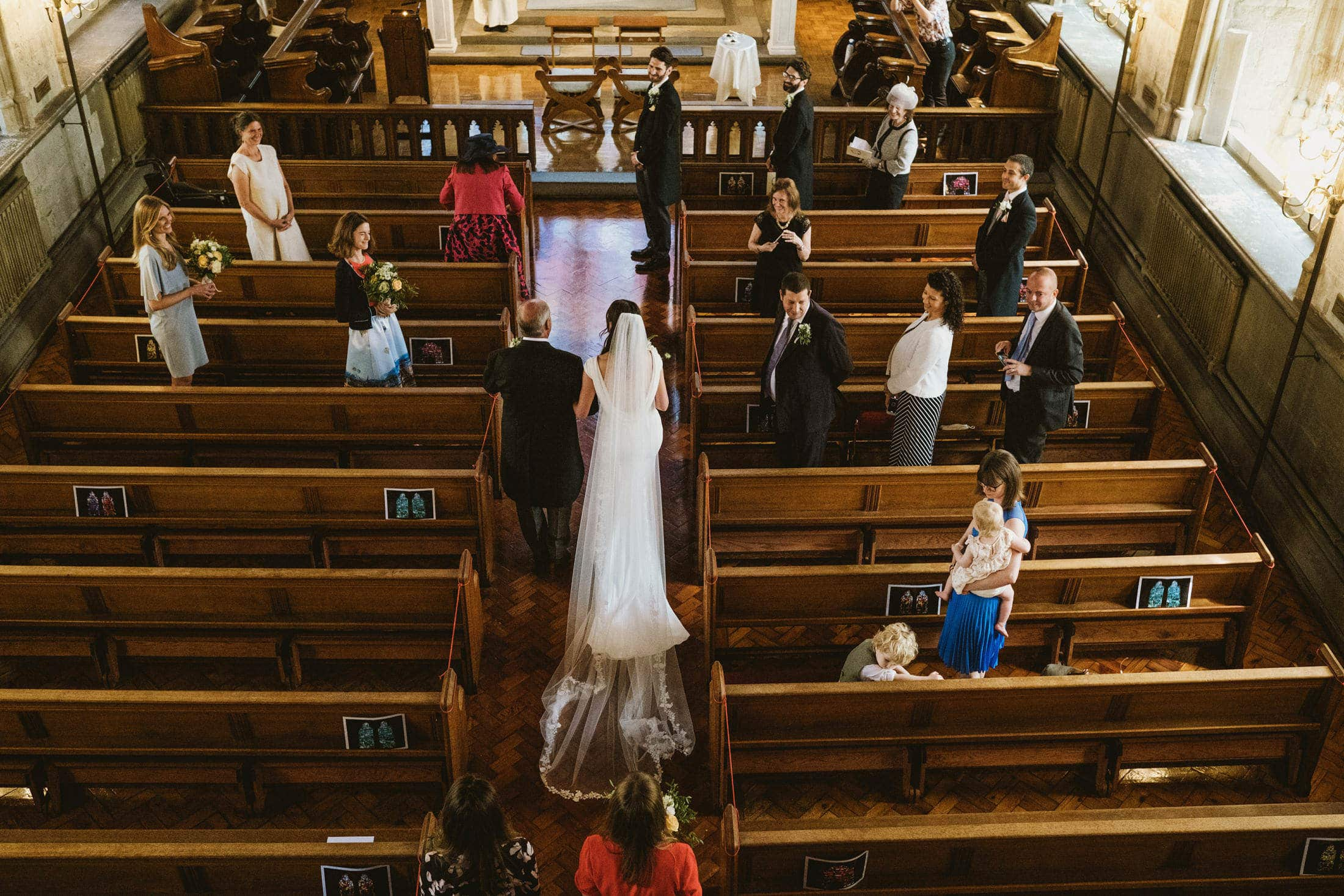Documentary wedding photograph of an Intimate London church wedding ceremony as the bride makes her entrance alongside her father. The smiling groom watches from the front as the socially distanced guests stand around them. Captured from the church balcony