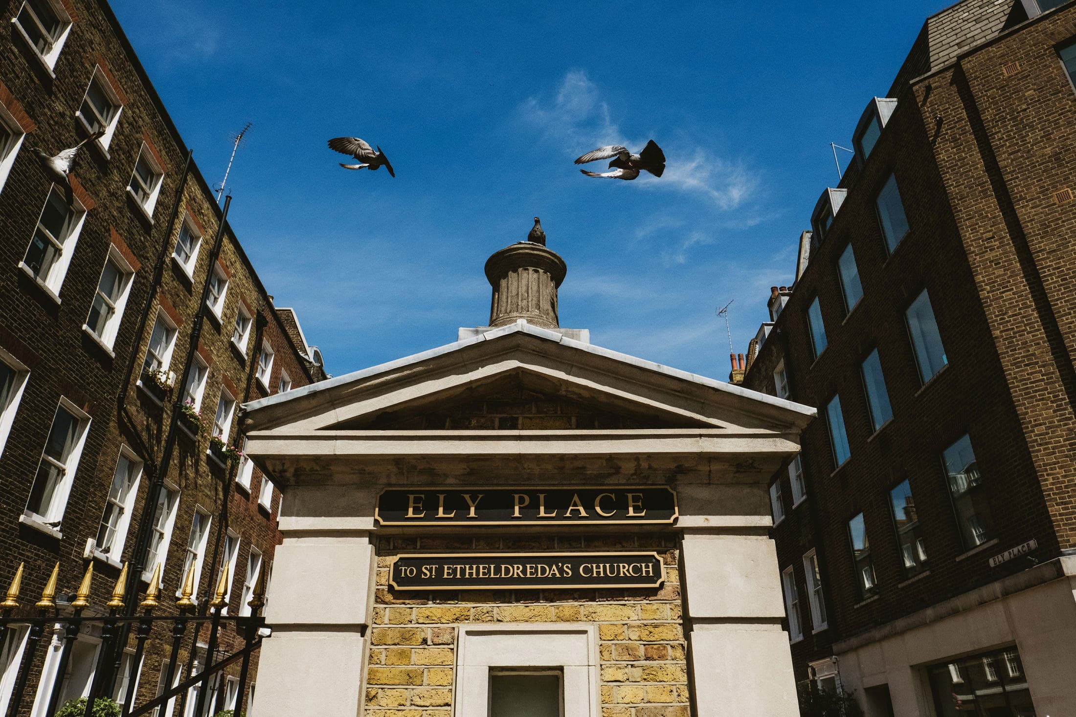 Birds fly over the entrance gate to St Etherelda's Church in London