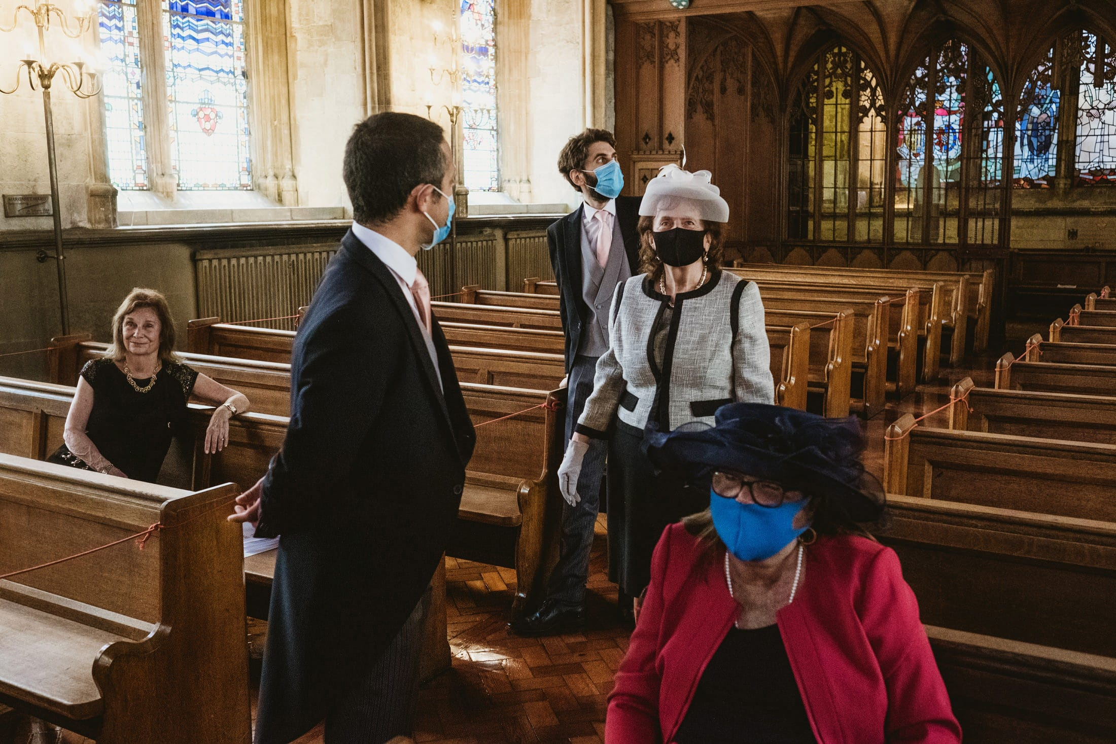 Guests assemble in a London church ready for an intimate London micro wedding. Four of the five people in the photograph wear face-masks due to being a covid-19 wedding. Micro wedding photography by York Place Studios