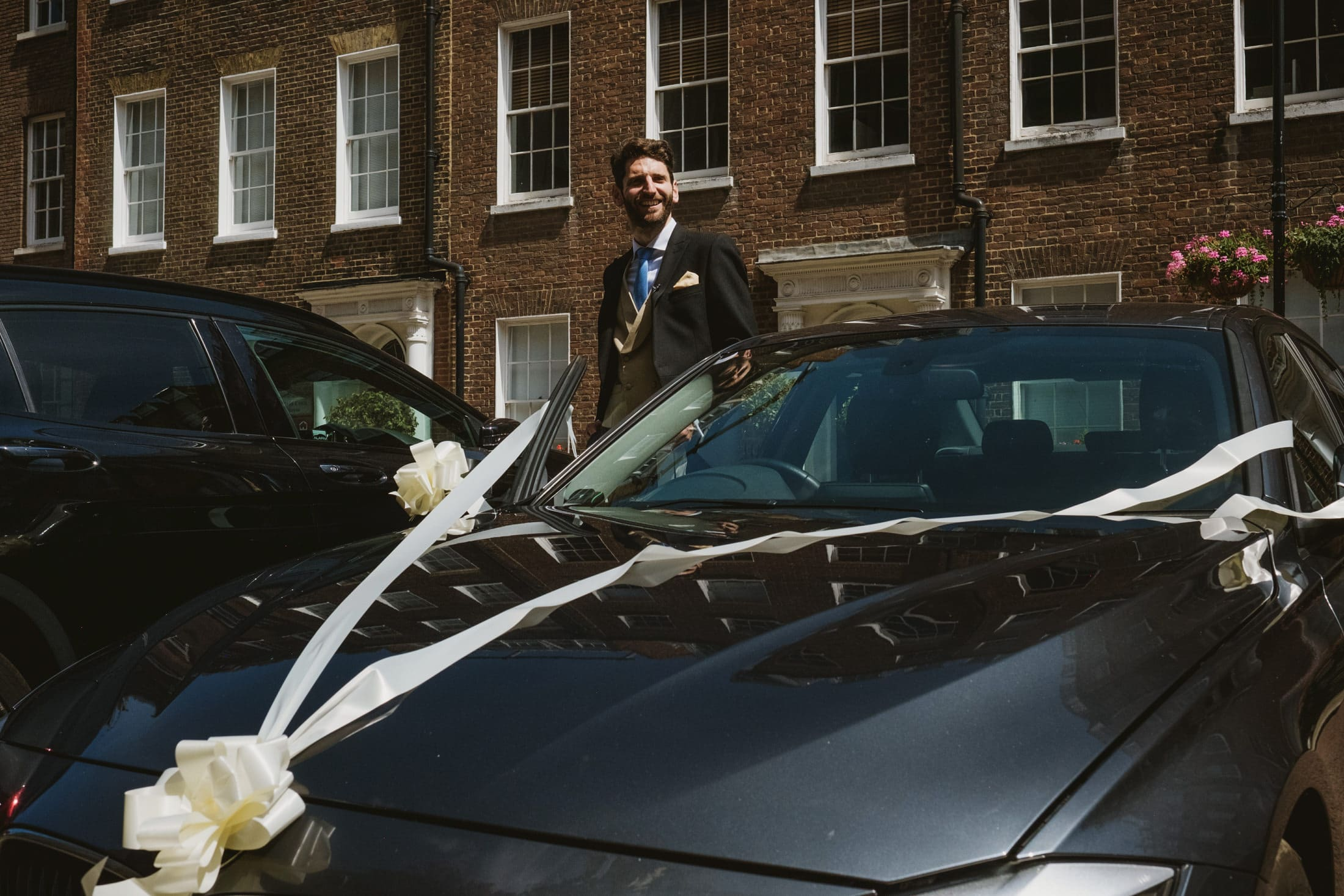 Groom stands beside wedding car prior to his micro wedding ceremony in St Etheldredas Church in London