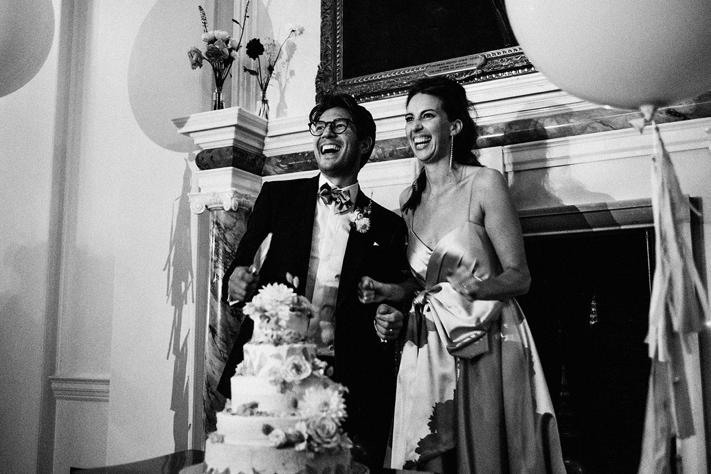 The Ned Wedding Photography London cutting of cake. Black and white wedding photo.