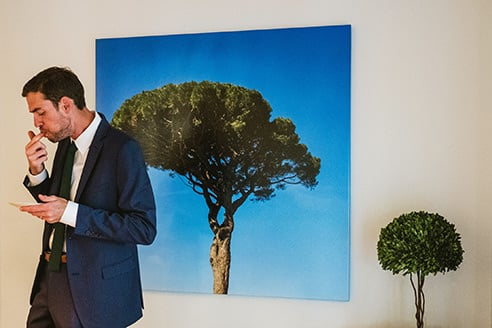 Reportage wedding photograph example. Groom stands on left of image in foreground. In the background a large printed photograph of a tree mirrors a real tree to the right of the frame