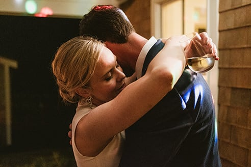 "Example of a completely unposed documentary ""portrait"". Bride and groom hug during wedding reception."