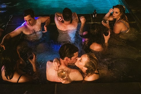 Example of a non-typical documentary wedding photograph. Bride and groom and guests enjoy themselves in a hot tub. Bride and groom kiss in centre of the frame whilst everyone else interacts, mostly with their backs facing the camera. One woman, top right, gives a sultry stare to the camera.