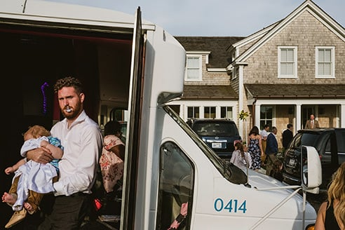 Example of a street style wedding photograph. In the foreground to the left of the image a guest steps out of a minibus holding a child in his arms. To the right guests are walking towards a house in the background