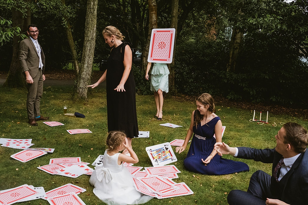 2nd Example of wedding photojournalism - Guests play with giant cards at a wedding reception. On the right of the frame a seated guest throws a card into the air and the photographer has timed the image so that the flying card covers another guest from the waist up. Two children are also sharing a moment whilst a male and female guest converse in the background.