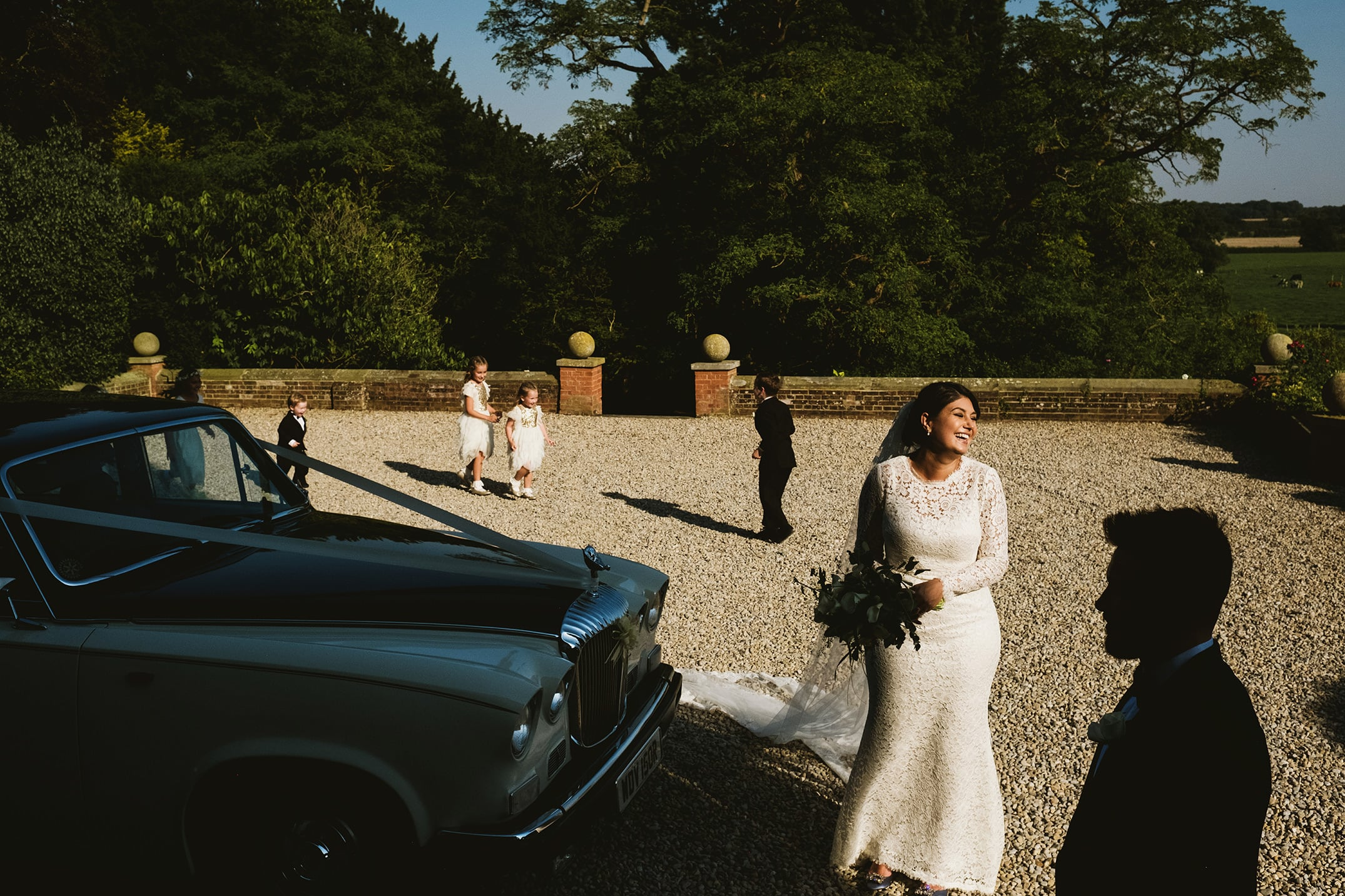 Documentary Wedding photography example image - bride next to wedding car with shadowed silhouette of groom in foreground to right of image. Four children play in the background. Courtyard setting with trees in background