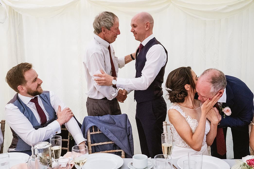 Example of Reportage wedding photograph taken after the speeches. Best Man sits to left of image whilst (centre) guest congratulates groom on his speech and they shake hands (both standing). To the right Bride (seated) kisses her father's cheek