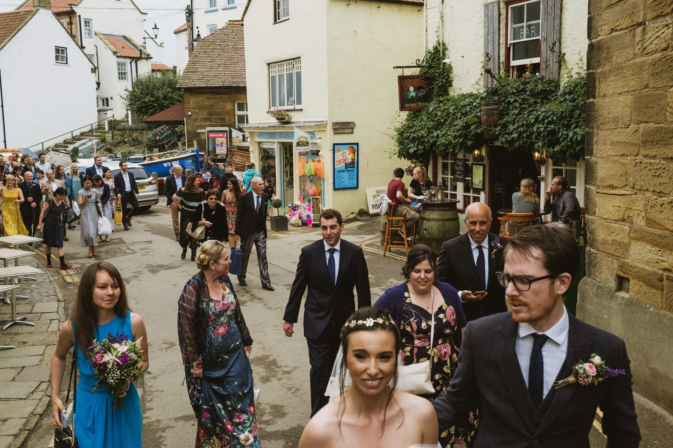 Bride and groom leading wedding guests to the reception. Robin's Hood Bay.