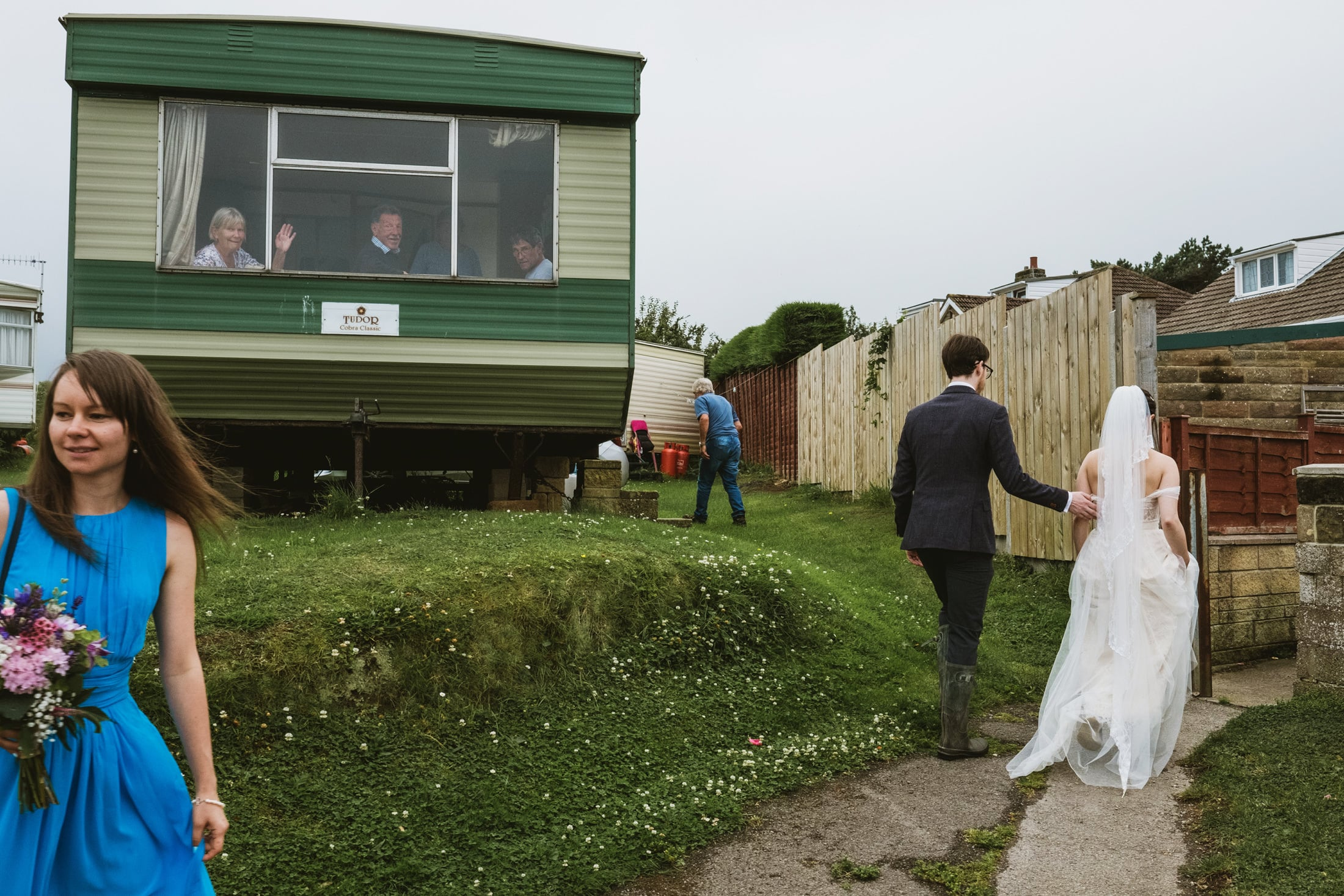 Bride and groom passing a caravan, people waving