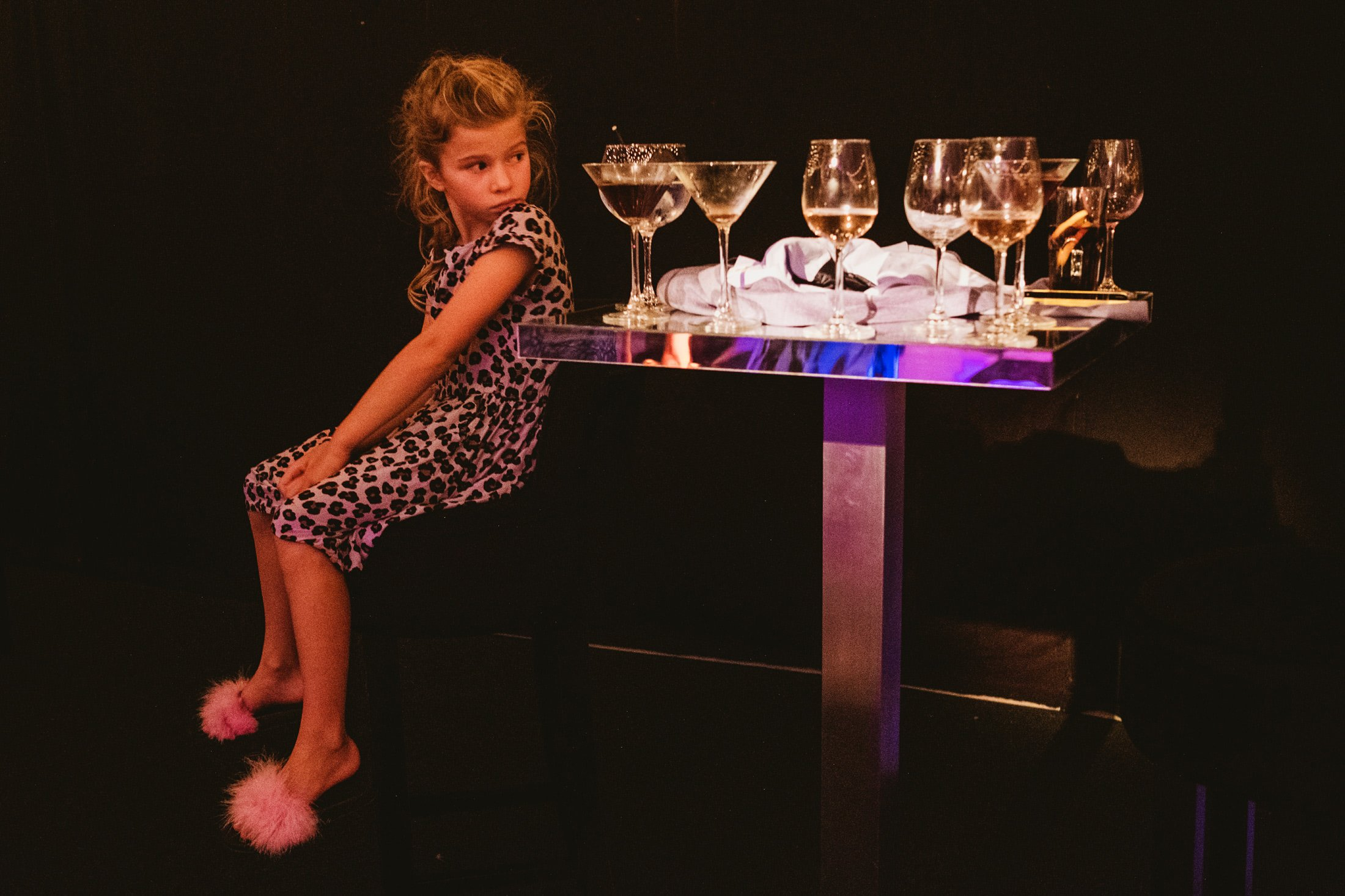 girl with wine glasses next to the dance floor