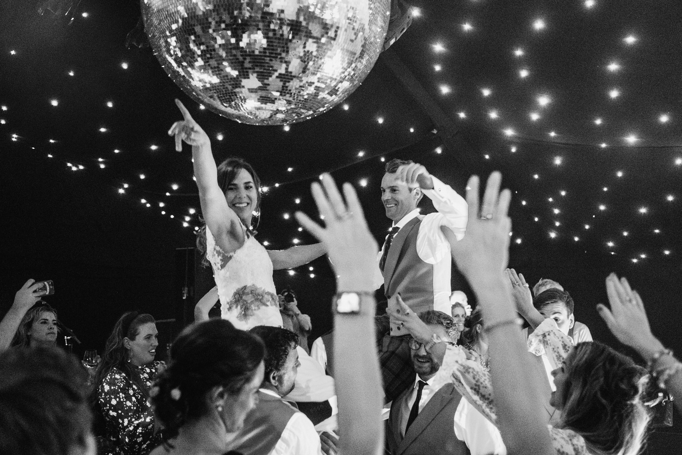 bride and groom being lifted in the air on the dance floor