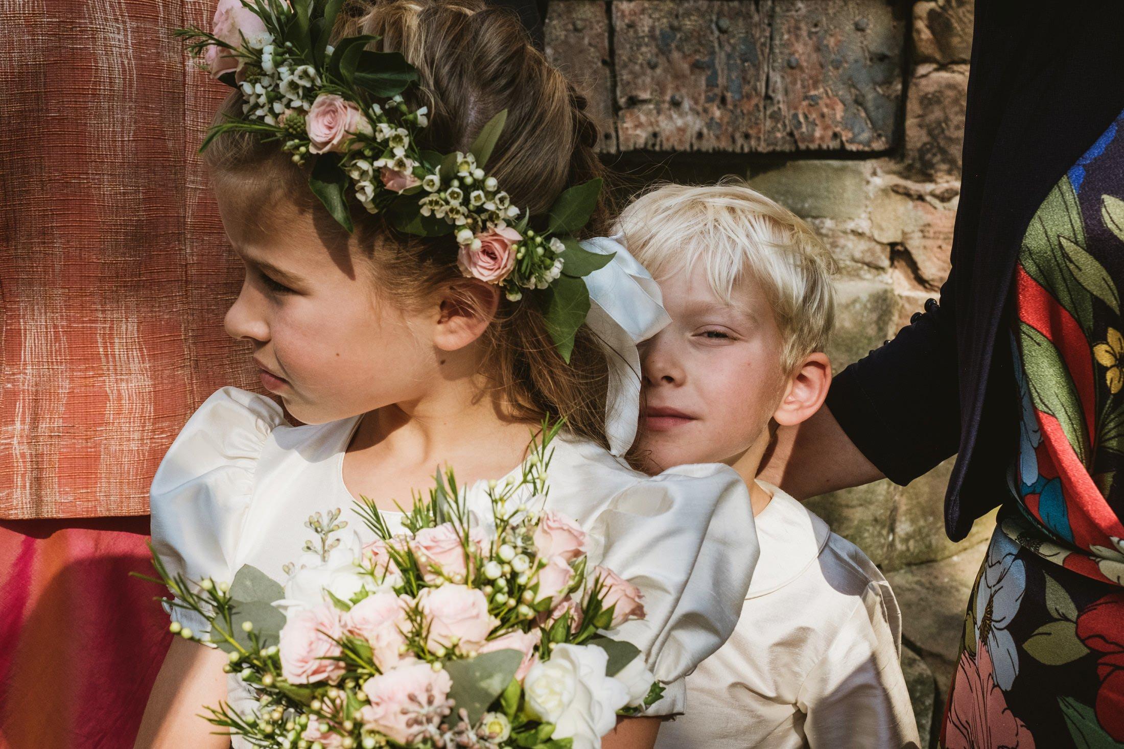 Cheshire wedding at church, page boy hiding behind flower girl