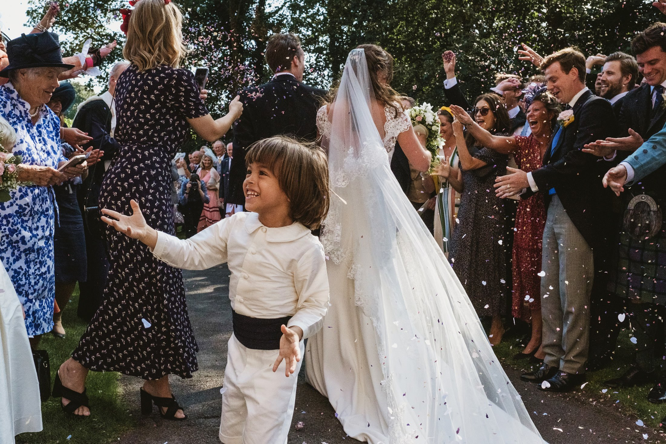 bride and groom running through confetti