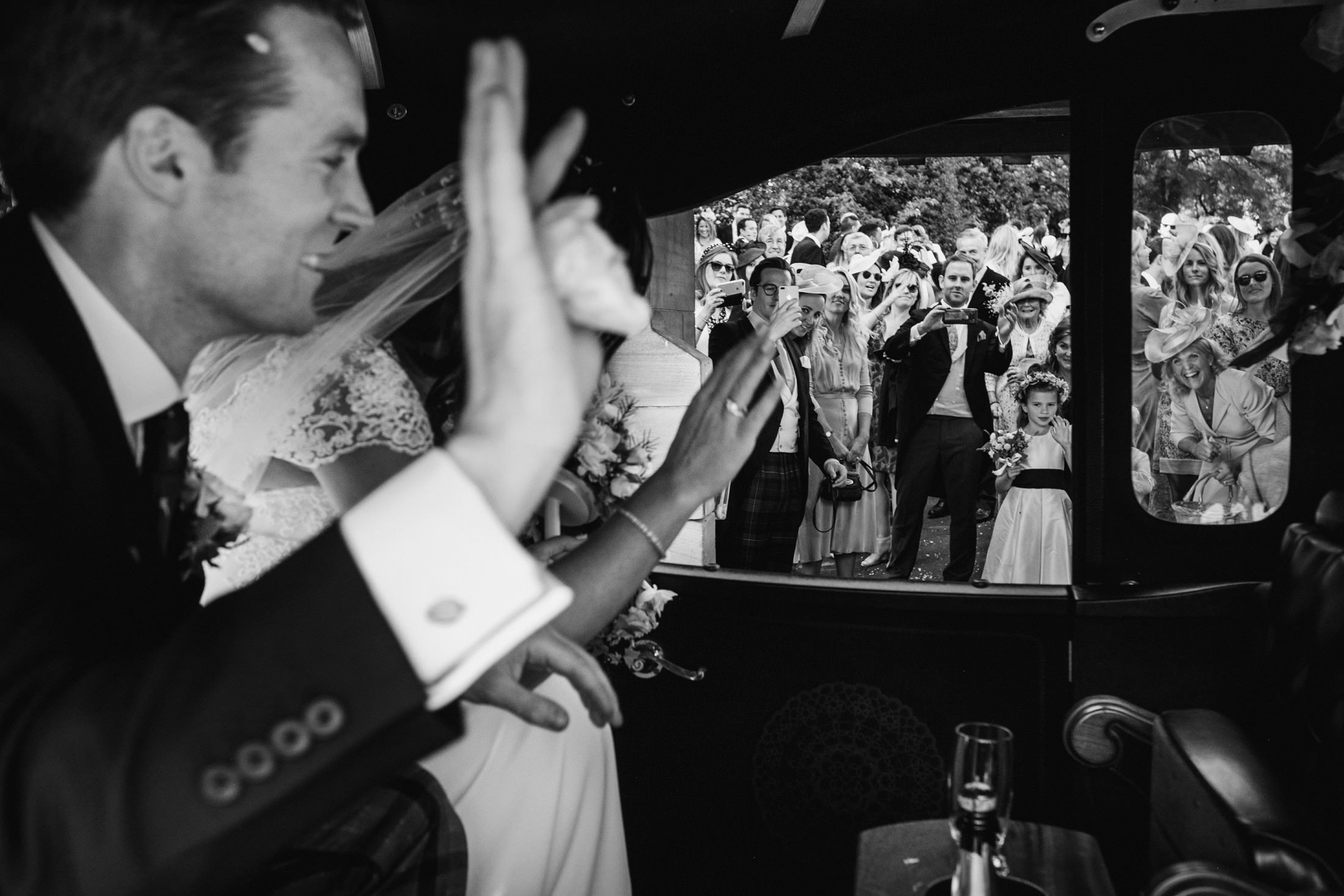 bride and groom waving their guests off in the wedding car in Cheshire