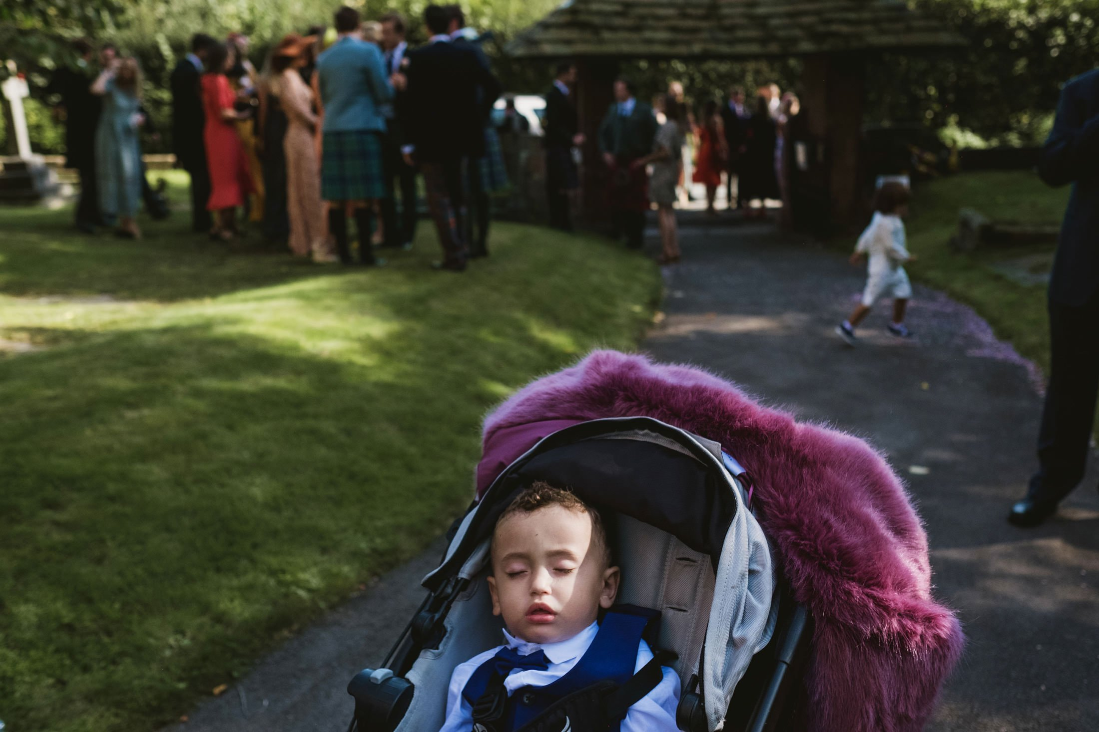 little boy sleeping in pram at church in Cheshire
