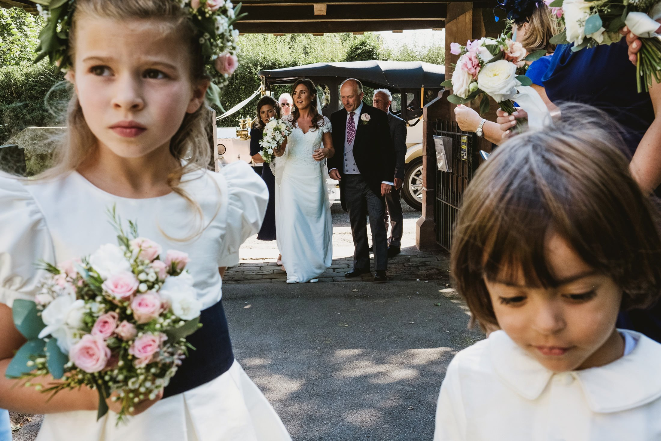 bride and wedding party arriving at church with flower girl and page boy in foreground.