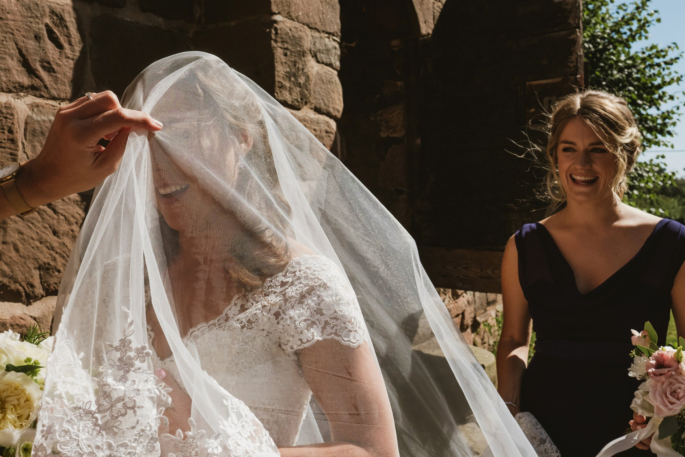 bride putting her veil on at the church