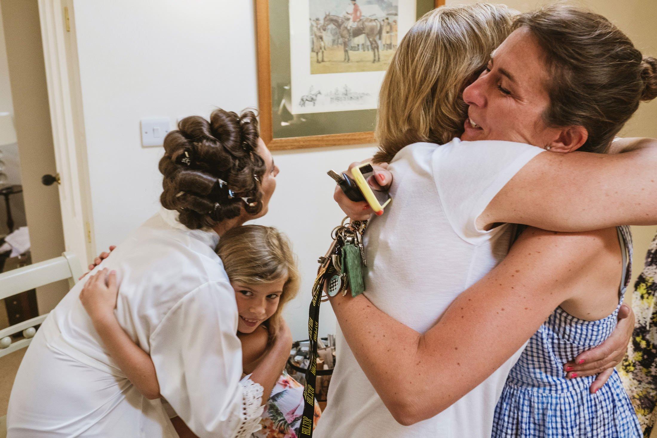 bride hugging flower girl and brides mum hugging parent