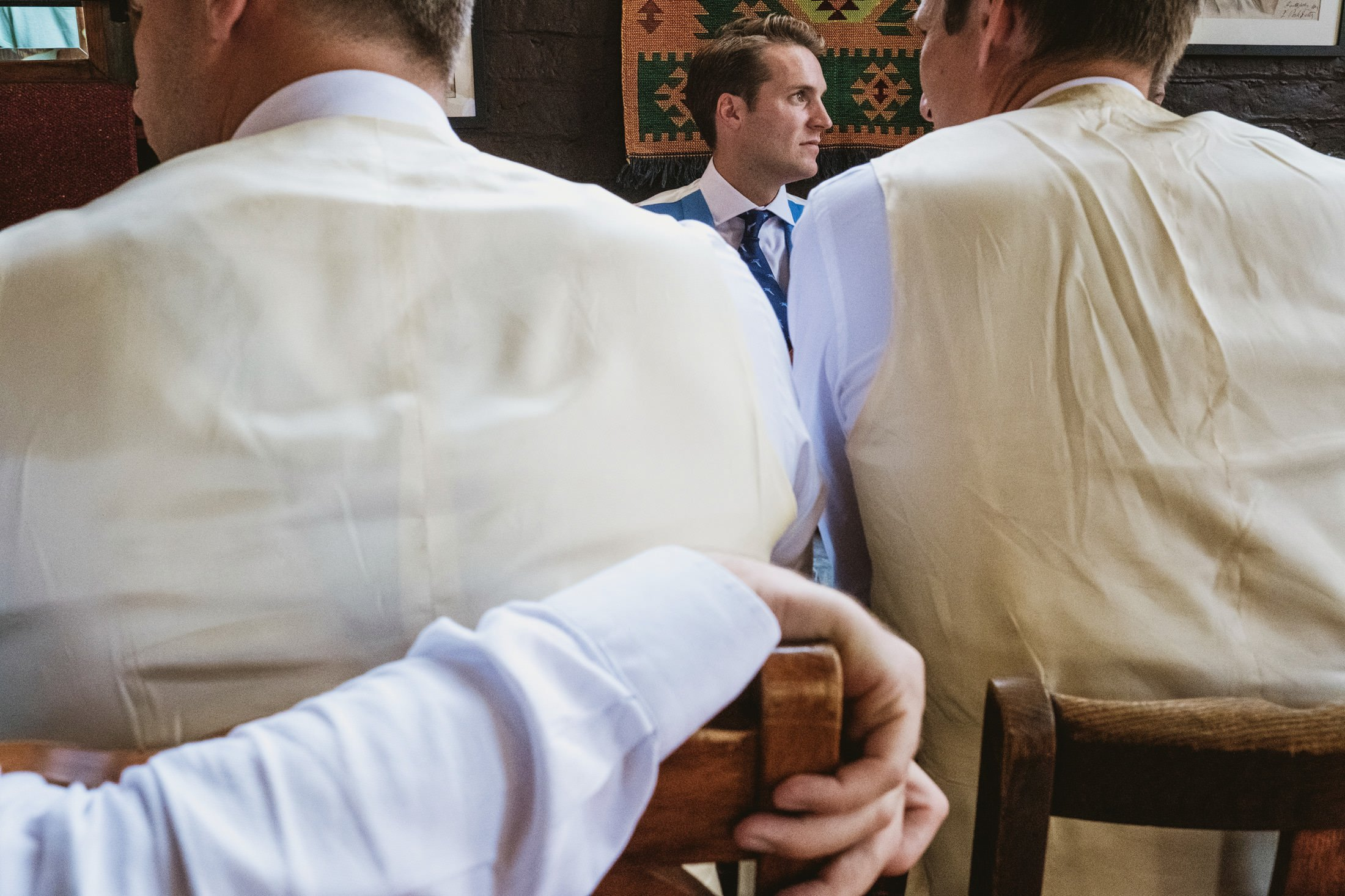 groom framed between two other people