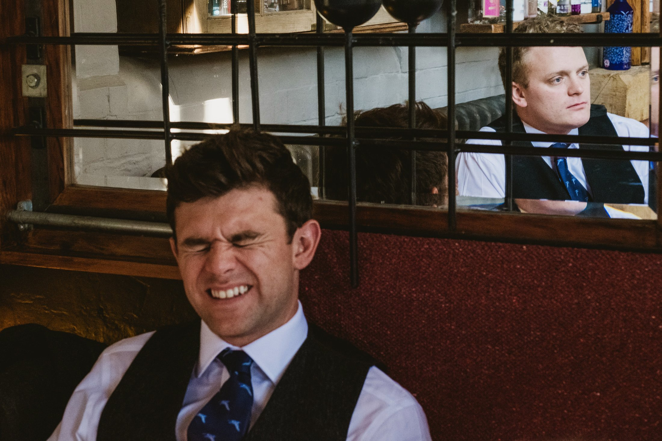 groomsmen, one laughing and one more serious