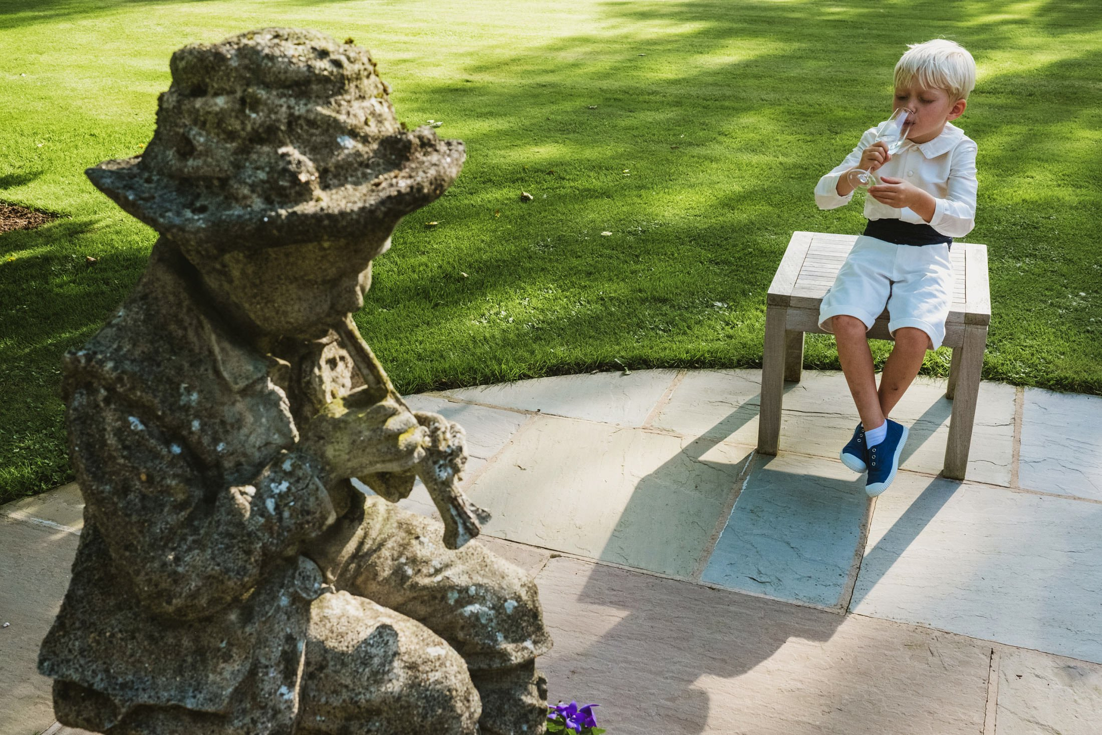 Documentary wedding photography, page boy drinking water in symmetry with stone boy playing a flute