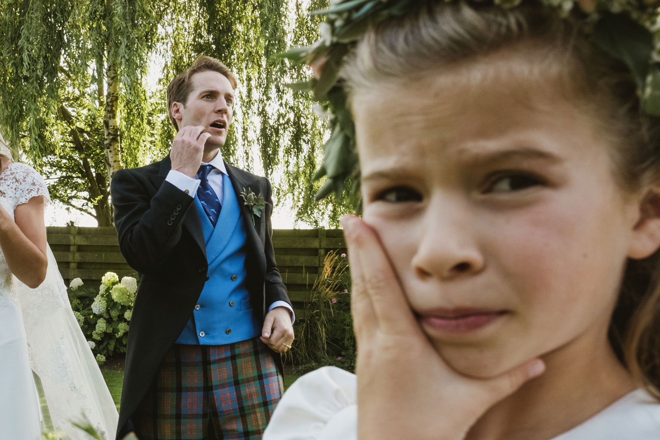 flower girl and groom both with hands to face