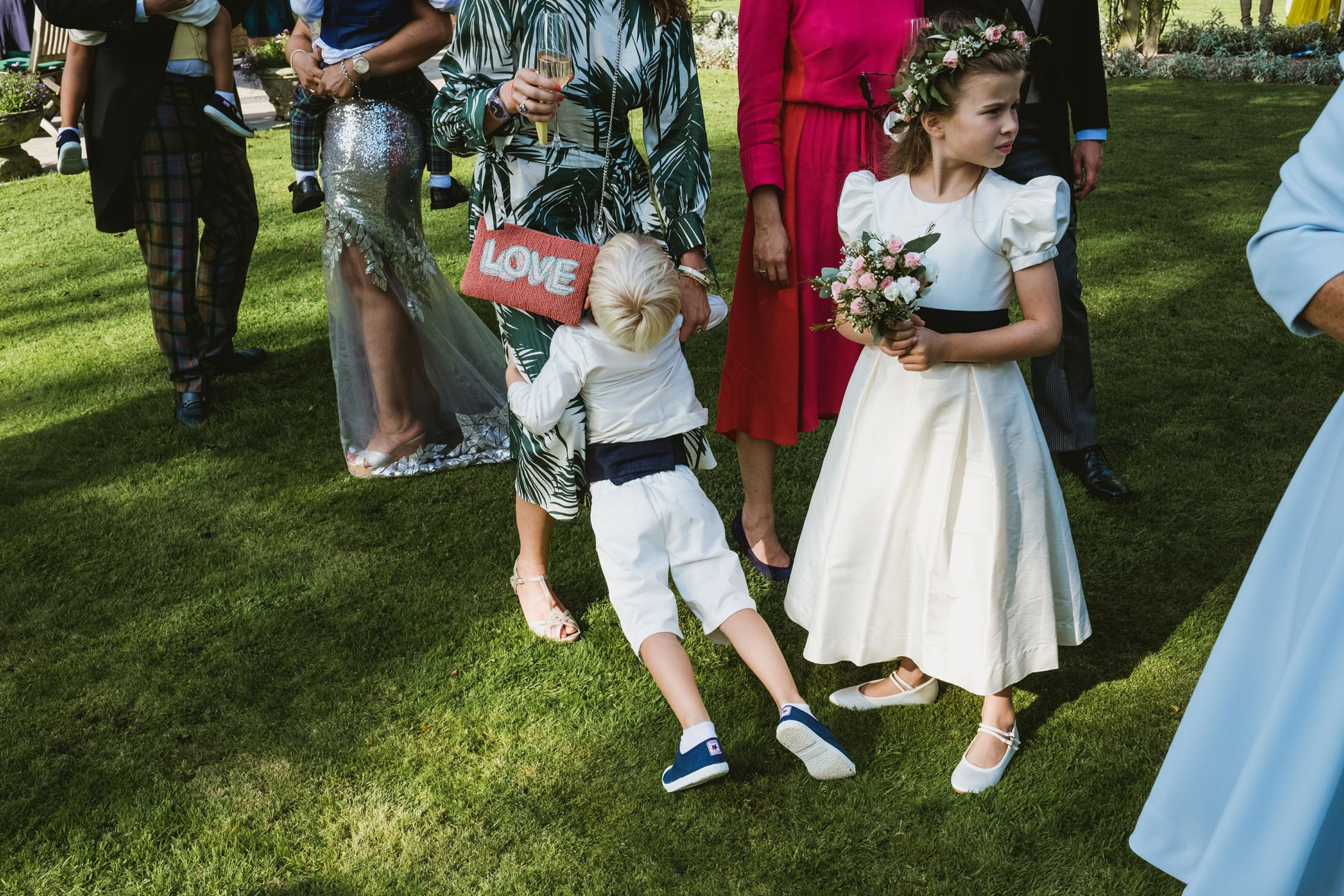 page boy leaning on his mum bored with flower girl next to them