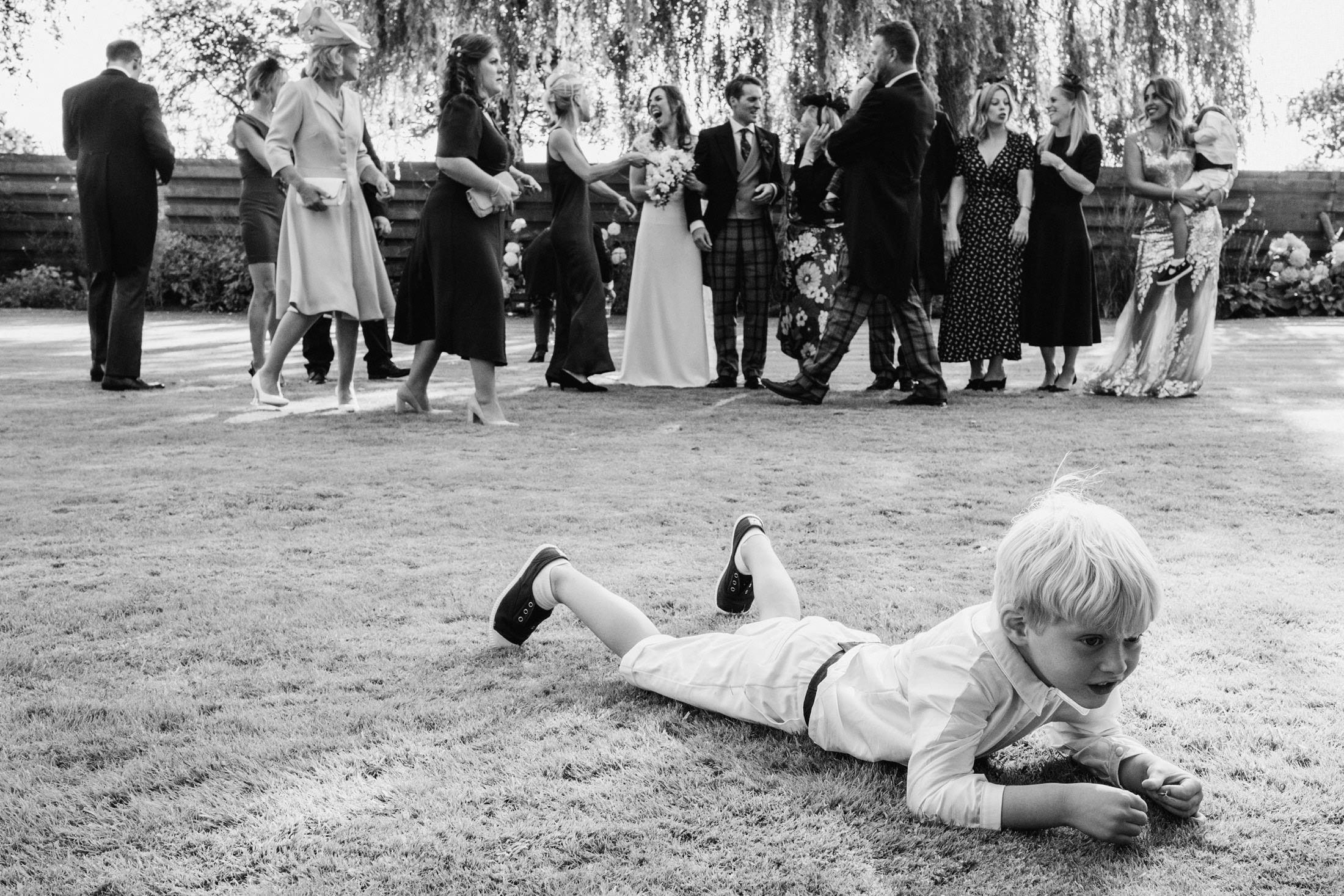 page boy on grass whilst wedding group is rearranged