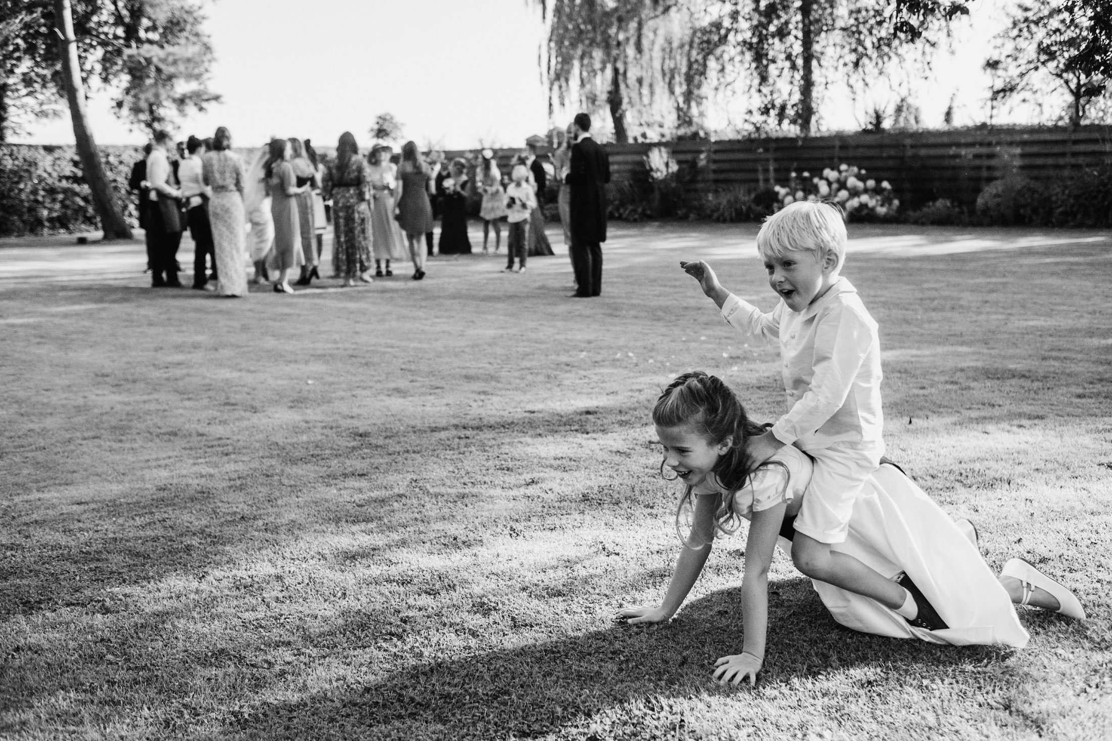 page boy on flower girl's back, whilst wedding group take place in a Cheshire wedding venue