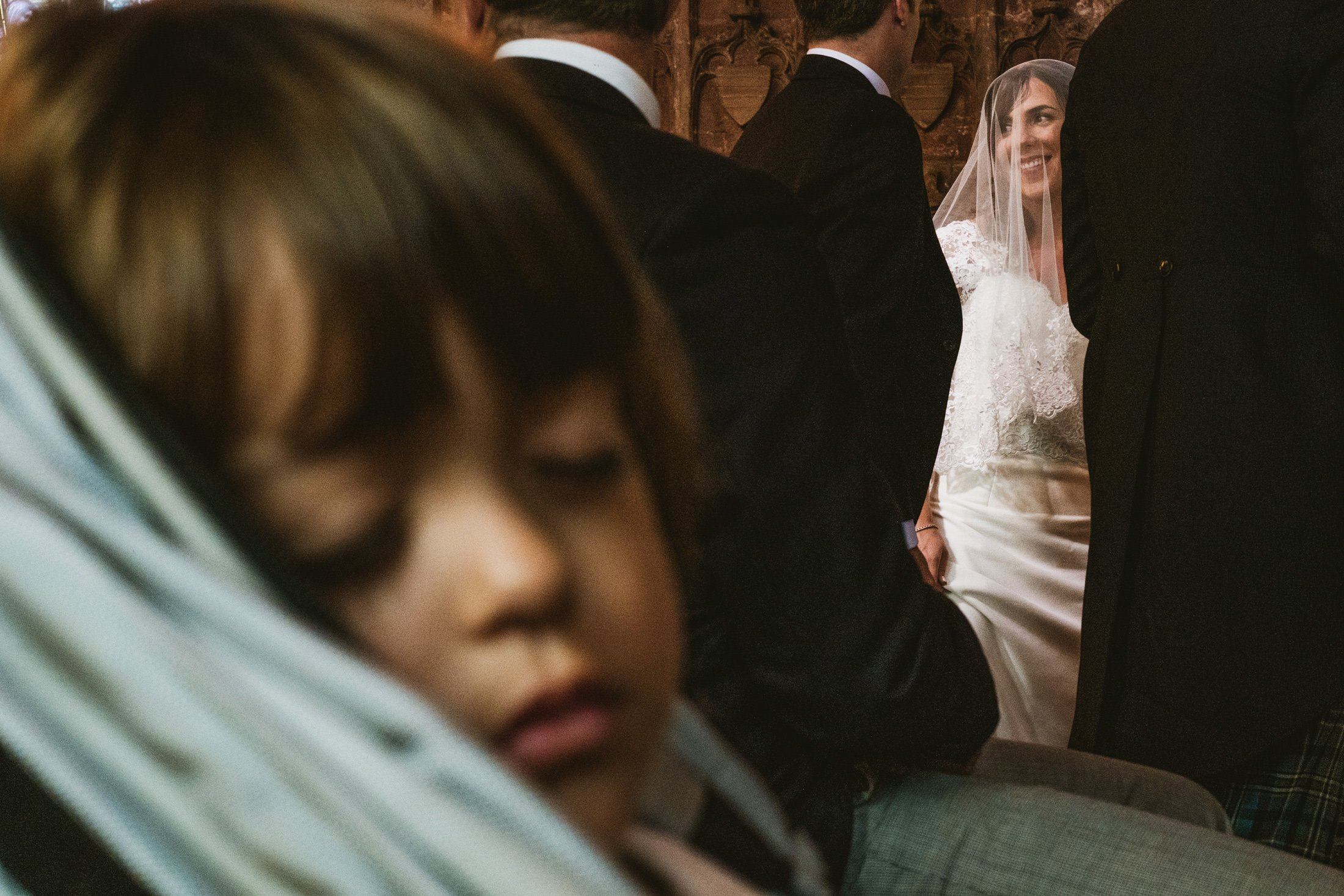 Cheshire documentary wedding photography, little boy sleeping during the ceremony, bride in background