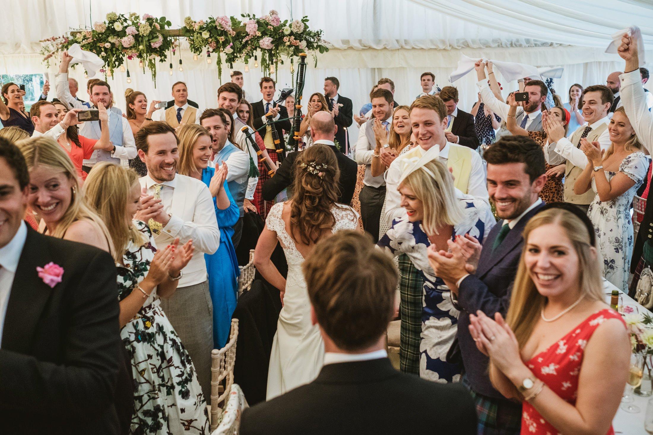 bride and groom wedding entrance, wedding guests all cheering