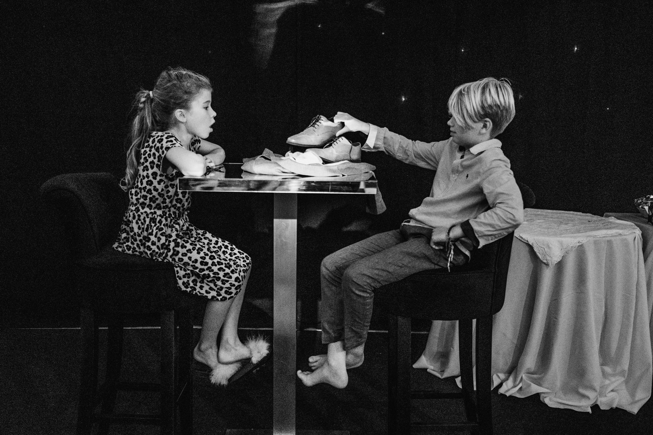 children sitting on stools next to dance floor