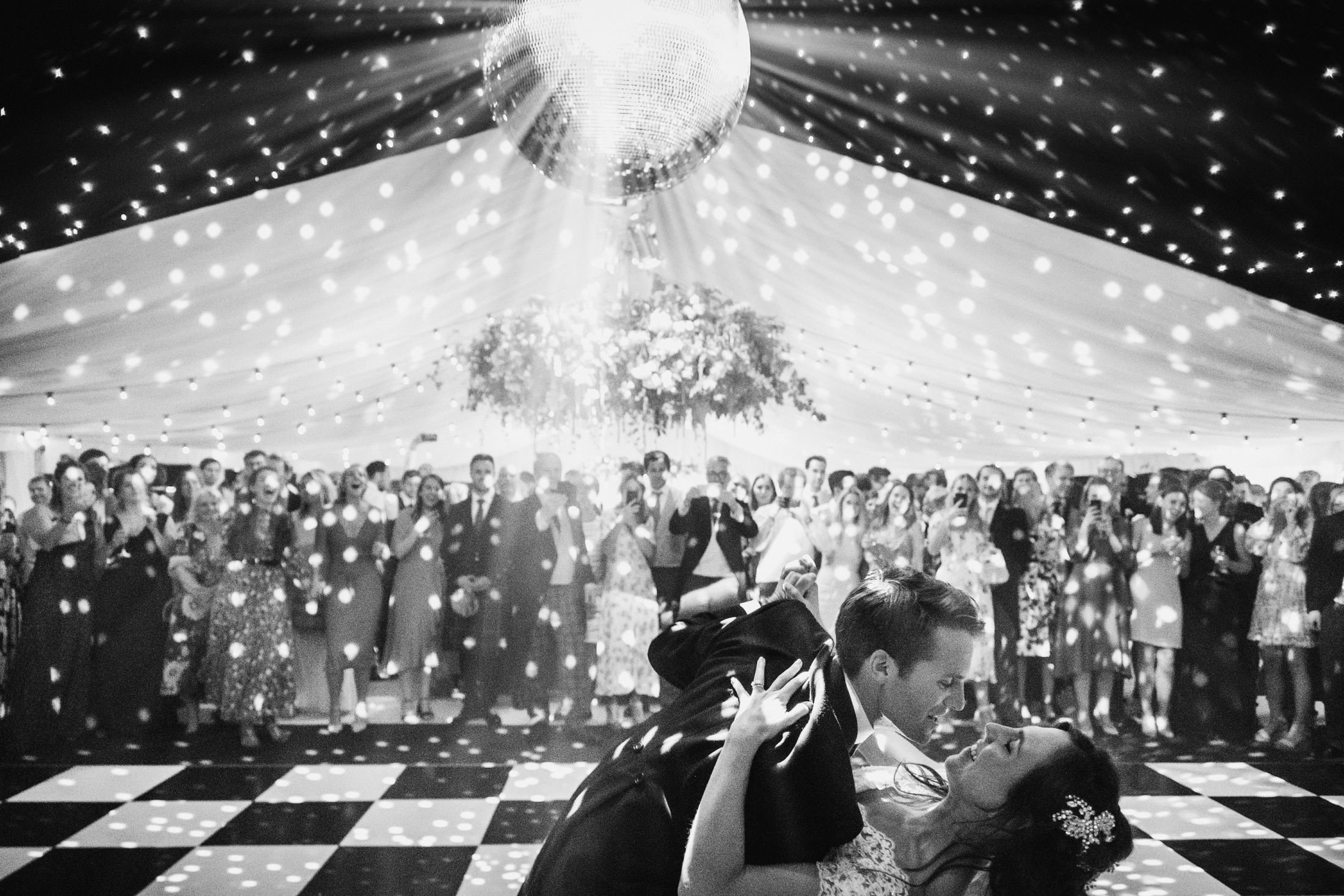 bride and groom first dance, groom dipping the bride with mirror ball