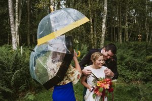 Comrie Croft Wedding Photography. Bride and groom together hugging with a wedding guest holding their umbrellas