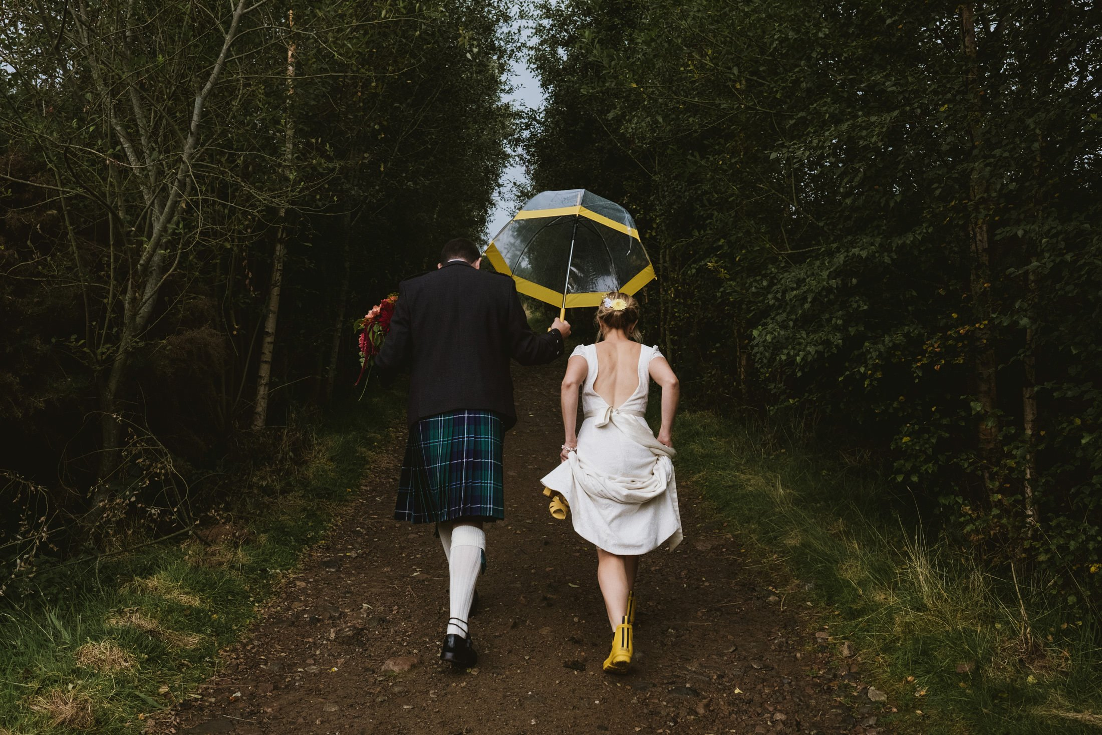 bride and groom walking, photographed from behind. Groom holding an umbrella.