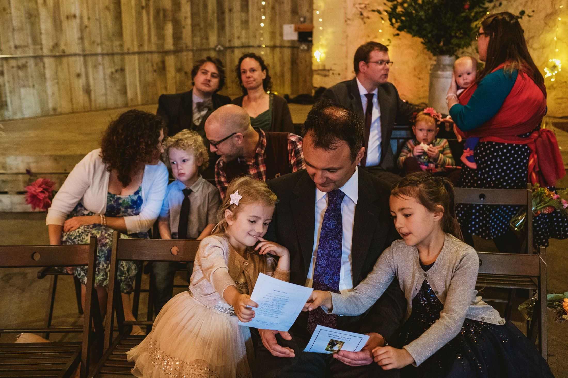 wedding guests looking at order of service before the ceremony at Comrie Croft
