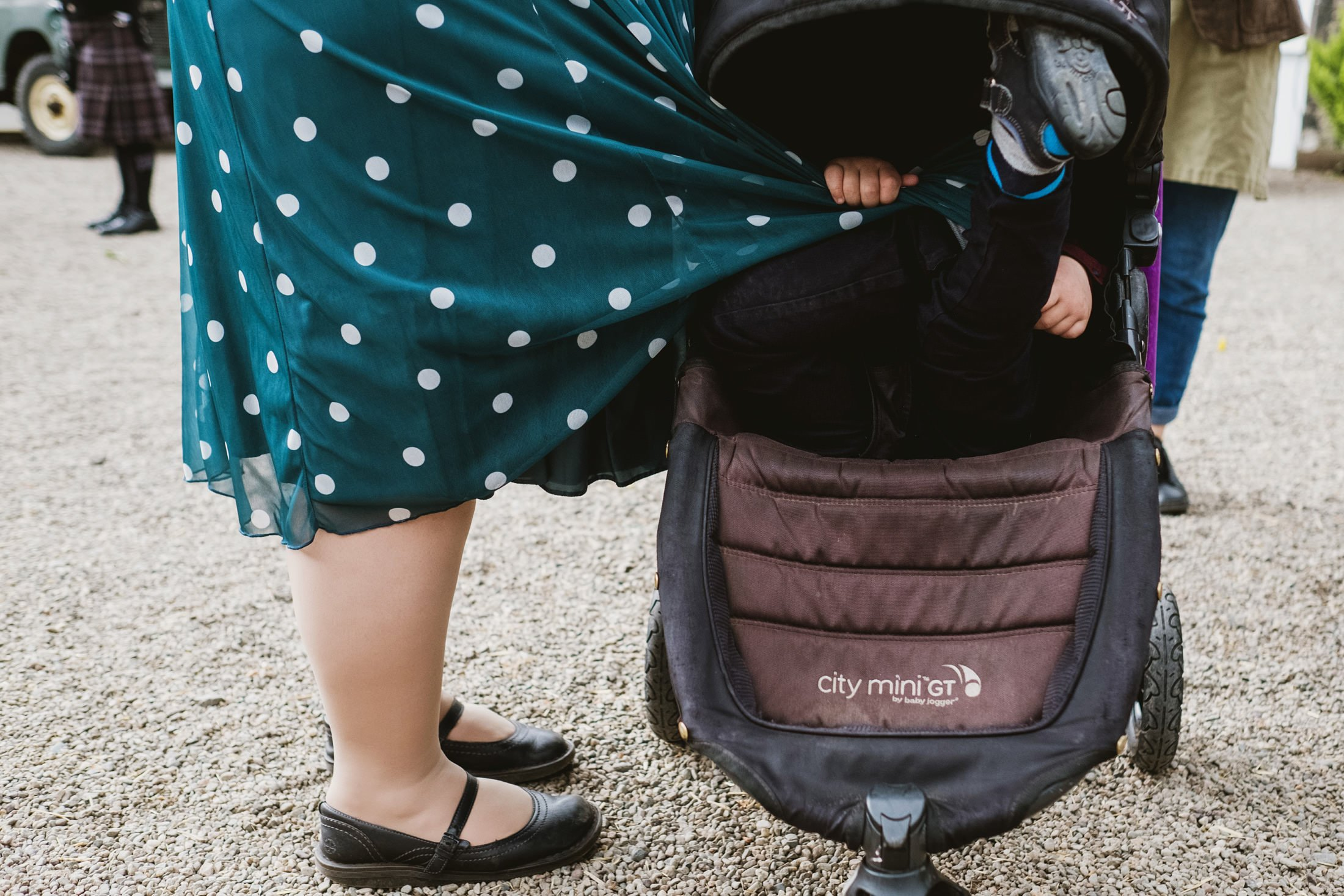 Playful reportage wedding photography. Little baby in the pram hiding under his mum's dress